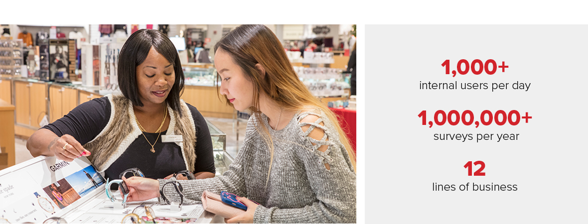 A photo of a Black, female sales associate with an Asian, female shopper looking at smart watches in the watch department.