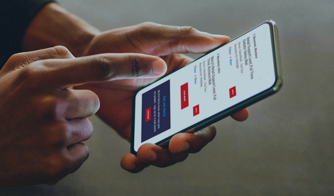 Close up of hands, one holding a smartphone and the other pointing at the screen that is showing job search results on the Macy's Jobs website.