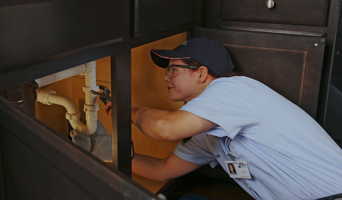 Female plumber wearing a navy baseball cap and light blue shirt using a wrench on a pipe under sink.