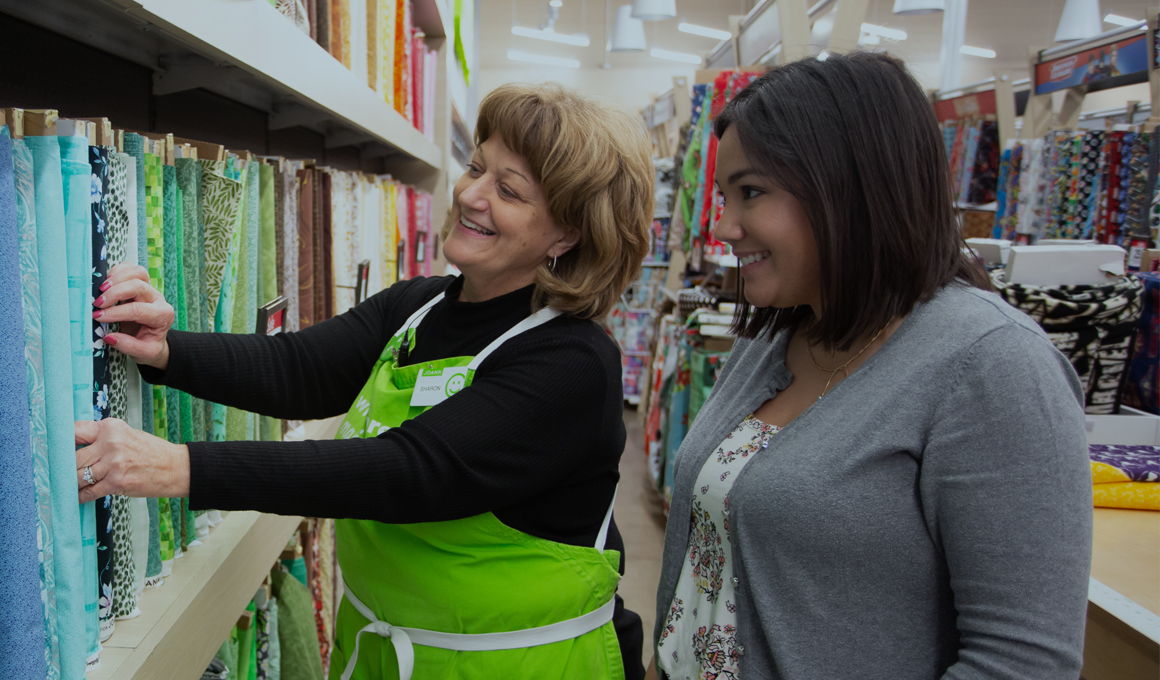 A JOANN team member wearing a bright green apron standing with a customer in the fabric aisle of a store, smiling.