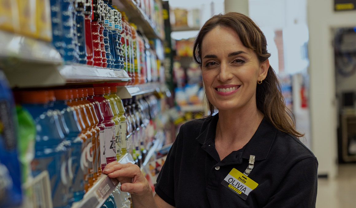 A smiling female Dollar General team member wearing a black polo shirt with yellow and white name tag that says Olivia standing in the beverage aisle in a Dollar General store
