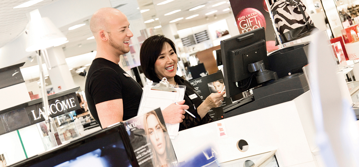 A cosmetics department manager teaches a sales associate how to use the point of sale system at Macy's. The manager is a tall, bald, Caucasian man and the sales associate is an average height Asian woman with chin-length black hair. Both are very polished, wearing black clothing and smiling.