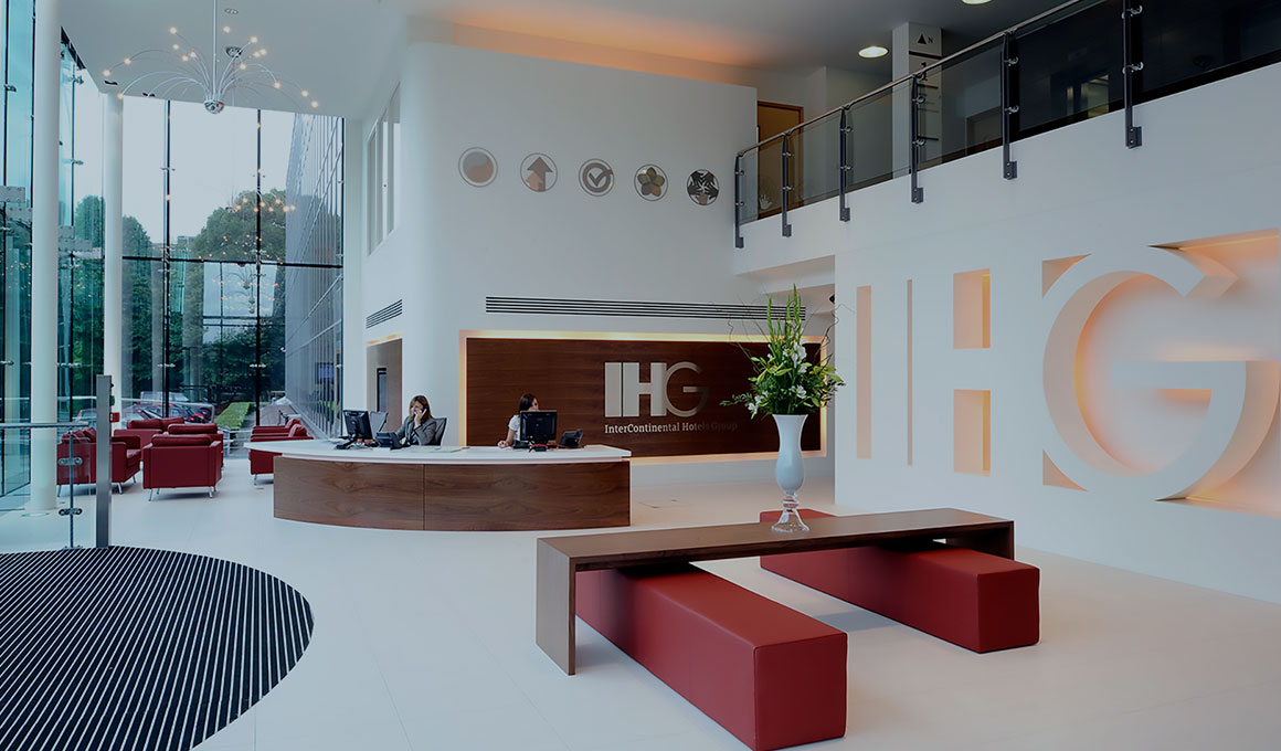 Two receptionists sit at the curved welcome desk in the lobby of the InterContinental Hotels Group corporate office. A large 3D version of the IHG logo serves as a dominant focal point.