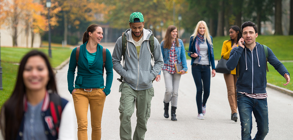 Photo of college students walking down a concrete path.
